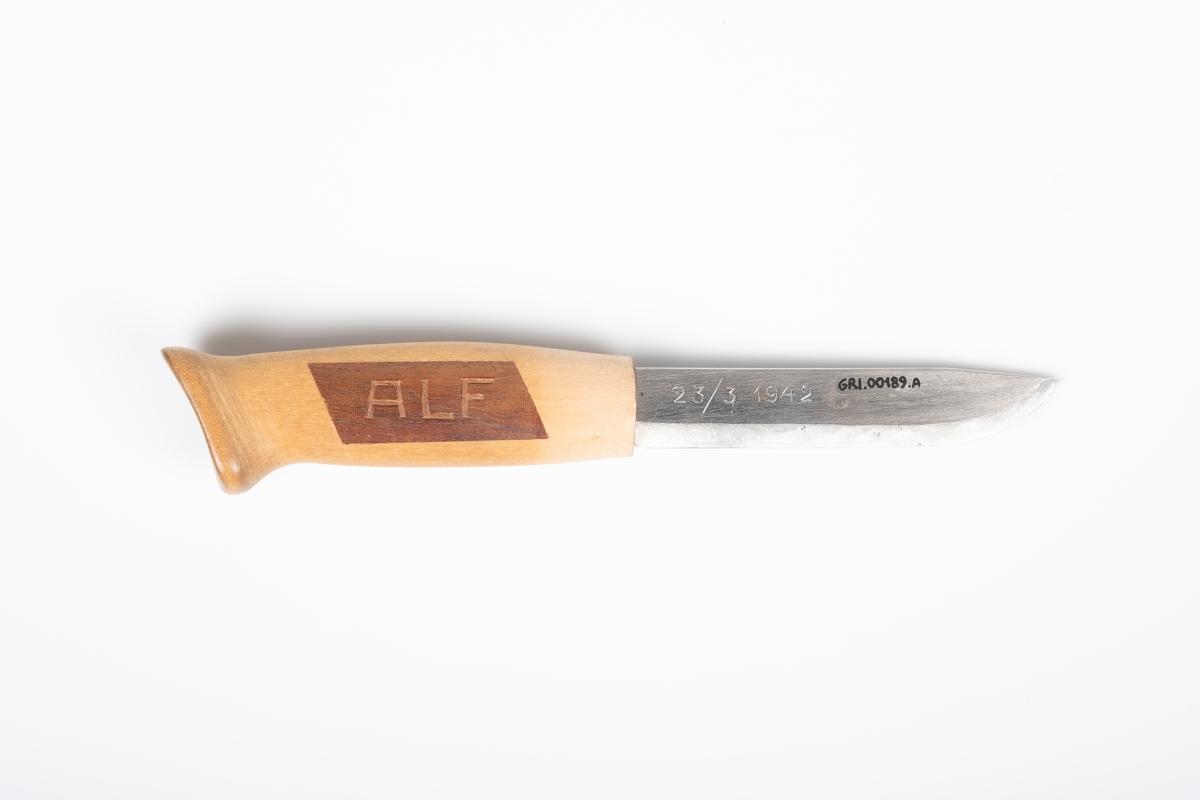 Håndlaget tollekniv med skaft og knivblad av metall. På hver side av skaftet er det et felt med et annet mørkere treslag. Det er ïnngaveringer på hver av feltene og på knivbladet.