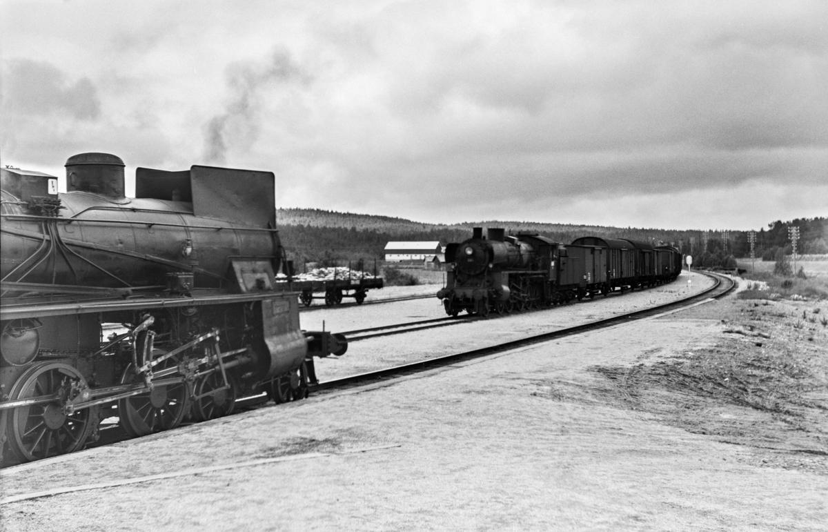 Kryssing på Os stasjon mellom godstog 5712 til Tynset og dagtoget fra Oslo Ø til Trondheim over Røros, tog 301. Godstoget trekkes av damplokomotiv type 26c nr. 399, tog 301 trekkes av type 26c nr. 413.