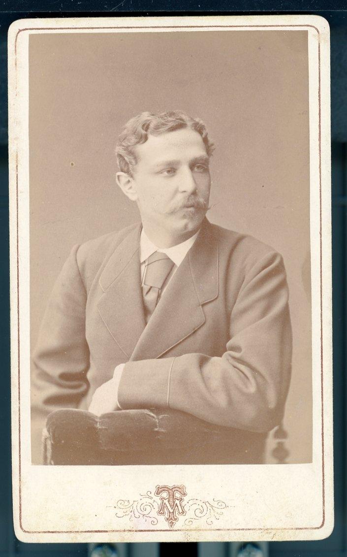 Kabinettsfotografi: Emil Kugelberg, sittande på en stol vänd mot dess rygg, blicken i fjärran.
