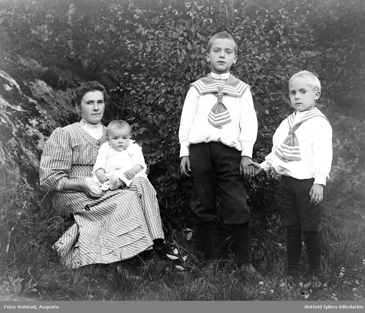 Gruppeportrett av mor med tre barn. Ukjente.
