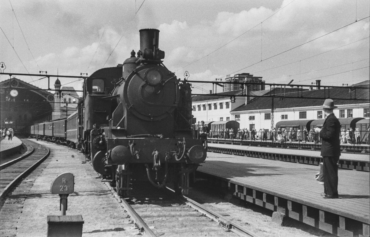 Persontog på Oslo Østbanestasjon. Toget trekkes av damplokomotiv type 32a nr. 283 (ekstra forspann) og 31b 446 (forspann).