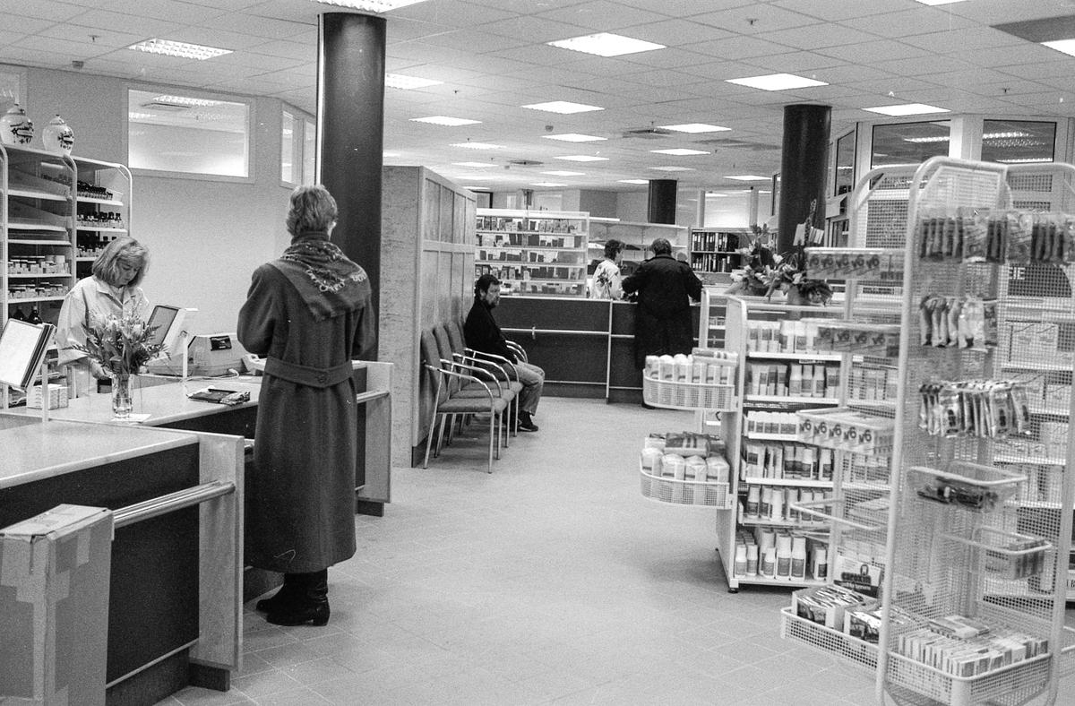Nytt apotek på Kolbotn-torget. Hyller med medisiner. Kunde i vinterkåpe.