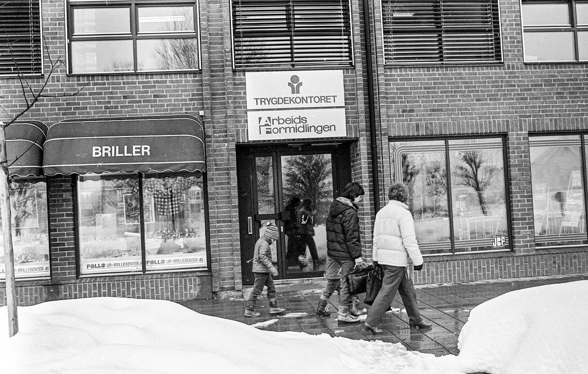 Arbeidsformidlingen for Follo. Kunder ved skranken får hjelp med papirer. Inngangsdøren fra gaten til Trygdekontoret og Arbeidsformidlingen.