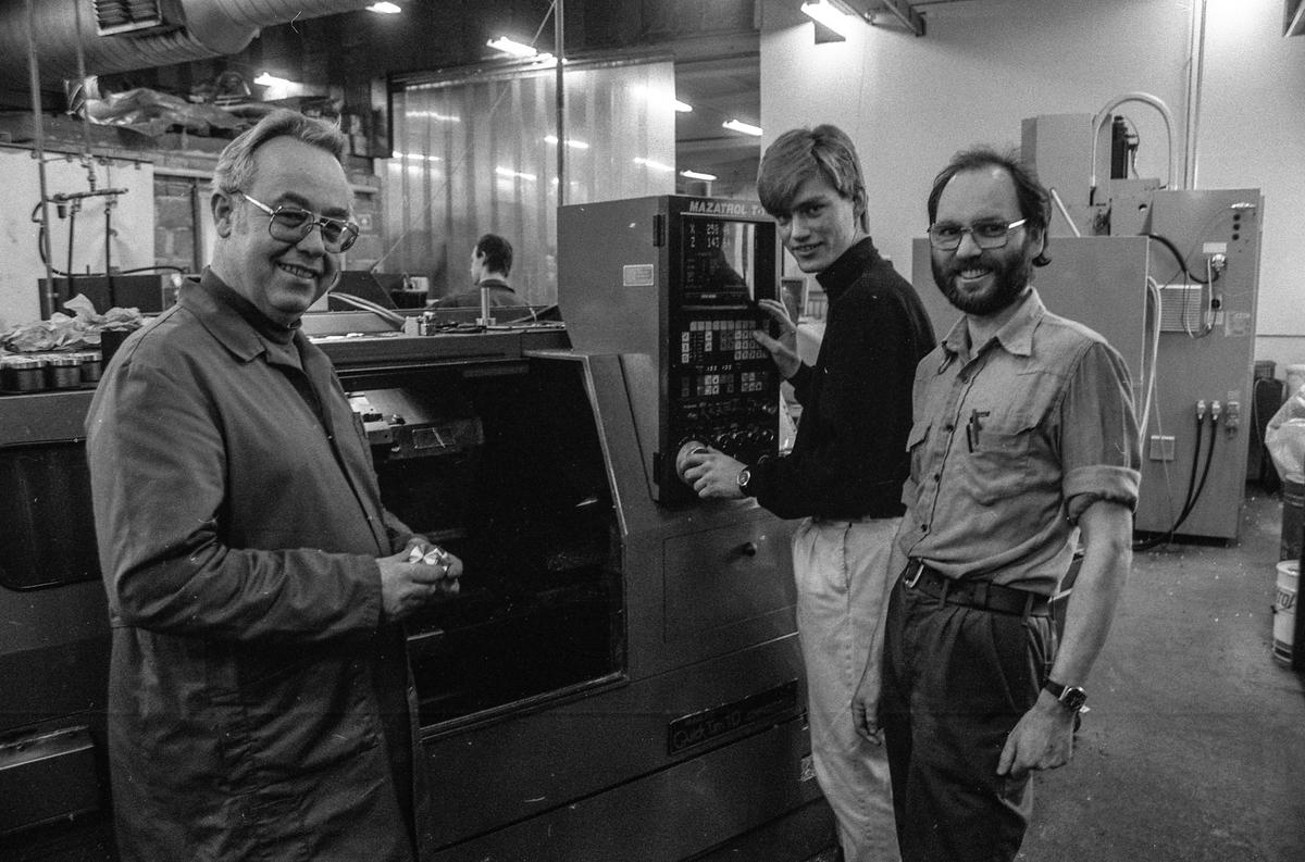 Follo Industriers første svenn, Rolf Erik Myhre fra Vestby, med fagbrev som maskinarbeider, inne i verkstedhallen, flankret av arbeidsleder Kjell Thorvaldsen (t.v) fra maskinavdelingen og dreier Odd Orvik som var ansvarlig for den praktiske opplæringen.