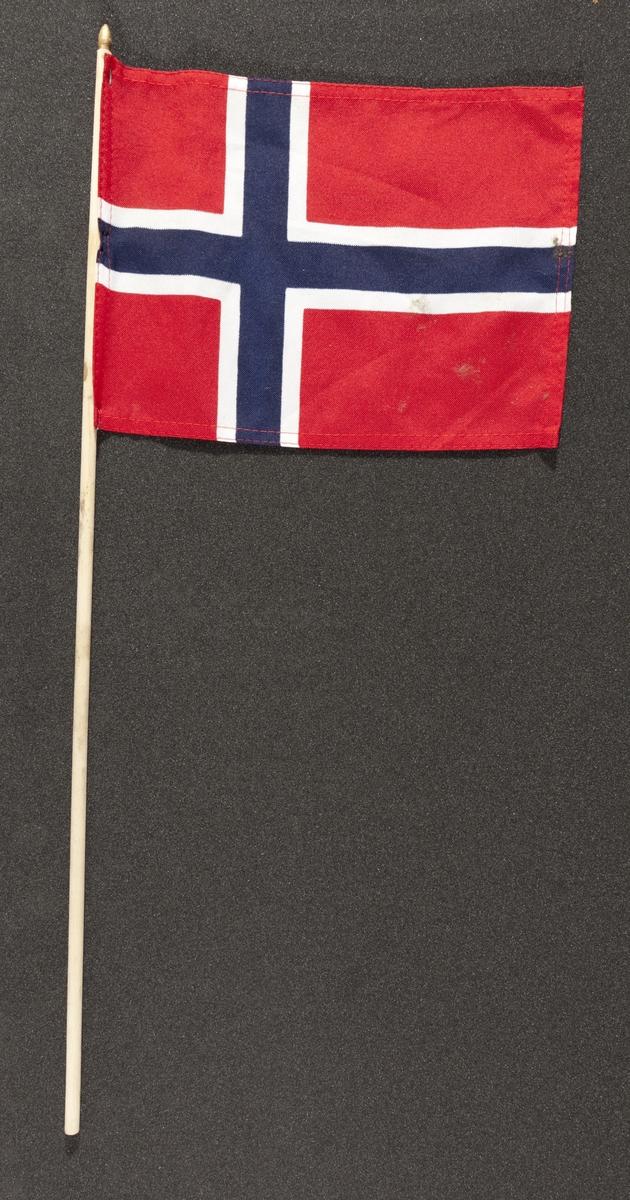 """Flagg innsamlet etter terrorhandlingen 22. juli 2011 fra minnesmarkeringene i Lillestrøm.   Klassisk norsk flagg slik vi kjenner det fra 17.mai feiringer: Blått kors i midten, hvitt kors som """"omkranser"""" det blå (litt tynnere fargefelt) på en rød bakgrunn, de blå og hvite korsene går helt til kanten av flagget. Dimensjonene på feltene er slik at de to røde felten mot pinnen er halvparten så store som de to ytterste røde feltene. Flagget brukes av både barn og voksne.Tuppen på pinnen som flagget er stiftet på er malt med gullfarge. Pinnen og flagget er blitt litt misfarget av opphold utendørs. Sømmene på flagget er røde."""