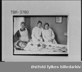 """Interiør fra værelse på sykehus, lasarett, ant. Moss sykehus i 1918. I protokoll er bestiller notert som """"For lasarettet"""". Tre sykepleiere står rundt død kvinne (ukjent), post mortem-portrett. Siden bildet er datert 1918, kan det ha med spanskesyken å gjøre."""