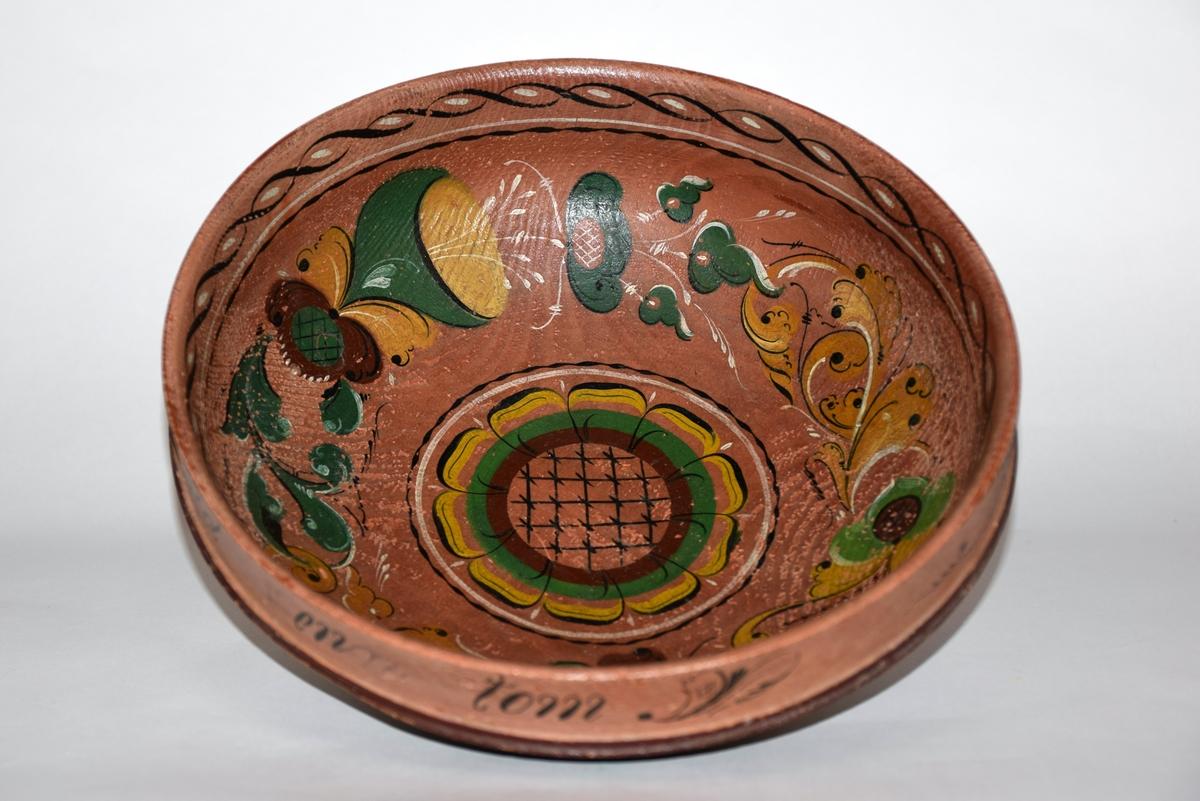 Rund trebolle med rosemalt mønster. Innvvendig bunnfarge og utvendig øvre kant i gammelrosa. Utvendig bunn mørk grønn.