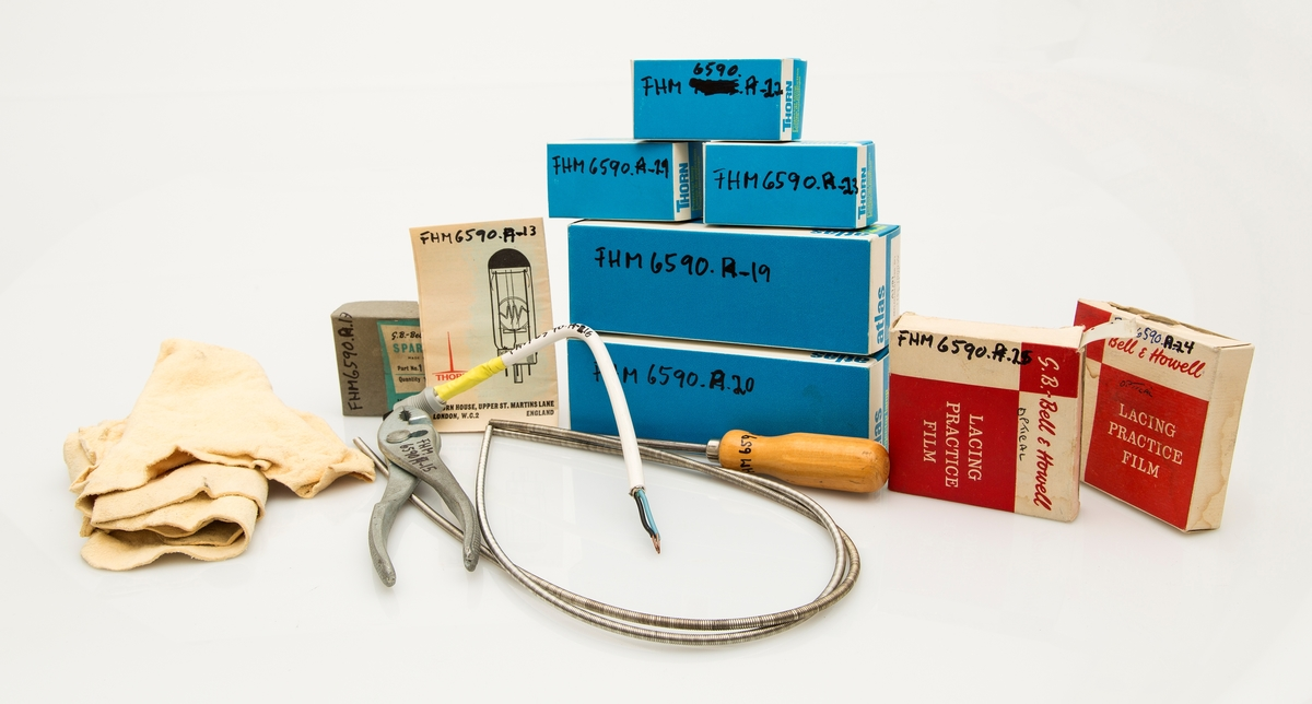 FHM.06590.a-1 16mm filmframviser type Bell & Howell 631 Sound Projector 16mm, i kasse med integrert høyttaler. Dessuten inngår FHM.06590.a-2 transformator, FHM.06590.a-3 vidvinkellinse i futteral, FHM.06590.a-4 metallholder til linse, FHM.06590.a-5 el-kabel til framviser, FHM.06590.a-6 bruksanvisning til fraviser, FHM.06590.a-7 stor filmspole, FHM.06590.a-8 liten filmspole, FHM.06590.a-9 strømbryter, FHM.06590.a-10 skjøtemaskin, FHM.06590.a-11 maskinisthøyttaler.                               Eske med utstyr: FHM.06590.a-12 pusseskinn, FHM.06590.a-13 bruksanvisning til reservepærer, FHM.06590.a-14 skrutrekker, FHM.06590.a-15 nebbtang, FHM.06590.a-16 kabelbit, FHM.06590.a-17 liten eske med reservedeler, FHM.06590.a-18 drivrem, FHM.06590.a-19 stor reservepære, FHM.06590.a-20 stor reservepære, FHM.06590.a-21 liten reservepære, FHM.06590.a-22 liten reservepære, FHM.06590.a-23 liten reservepære, FHM.06590.a-24 eske med filmfortom, FHM.06590.a-25 eske med filmfortom.