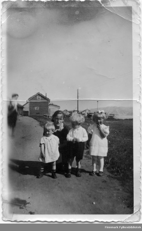 Fotografert i Skjøtningberg. Astrid Karlsen med tre barn. Astrid Karlsen, født Lund var gift med Valter Karlsen. Bryllupet ble holdt i Oksvåg. Bjarne Mikkelsen og kona var i bryllupet, iflg. Leif Roald Aslaksen, ref. blogg: http://rafsbotn-historie.no/Dagbok_1944_Farvel.html Tidligere eier av bildene var Kjøllefjord historielag. Informant er oppgitt til Valter Karlsen, mannen til Astrid.