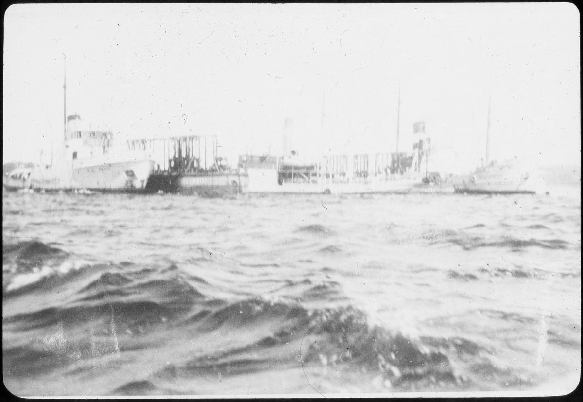 6 skip som ligger fortøyd ved siden av hverandre, åpent hav.
