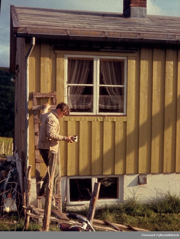 """Kunes, sommeren 1963. Maling av huset til Petter Karlsen i Henriksbukta. Personen på bildet er ikke identifisert. Kunes (samisk: Gussanjárga) er en bygd i Lebesby kommune i Finnmark. Stedet ligger innerst i Storfjorden. Fylkesvei 98 passerer igjennom Kunes. Fotografen, Richard Bergh, har også skrevet et hefte som heter: """"Når vi sitt' her og prate"""". Folk i Laksefjord forteller. Norsk Folkeminnelags skrifter nr. 122. H. Aschehoug & Co. (W. Nygaard). Oslo 1980. ISBN 82-03-10187-9. Fylkesbiblioteket har også et flyfoto av Petter Karlsens gårdsbruk, tatt av Widerøe Flyselskap:  Bilde: FBib.93104-015"""