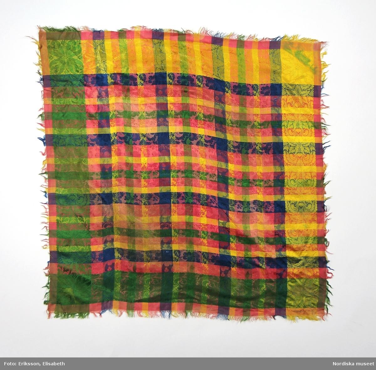 A-F Flickdräkt  A. Livstycke B. Överdel C. Kjol D. Förkläde E. Halskläde F. Bindmössa    E. Halskläde 73 x 73 cm rutigt sidenkläde i gult, rosa, blått och grönt med invävt yttäckande mönster, olika i bård och spegel.  Berit Eldvik juni 2005