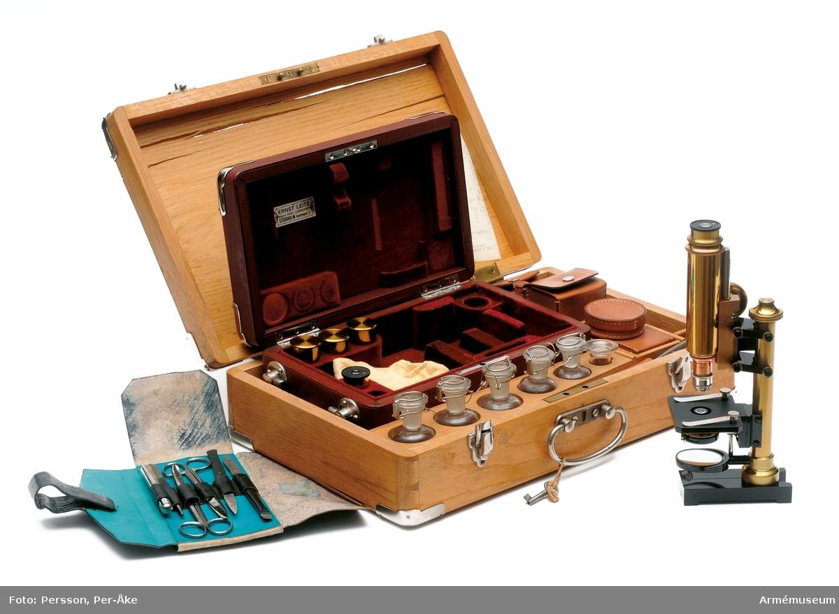 """Träväska med lås, märkt i locket: """"Ernst Leitz, Vertr. Frz. Bergmann. Berlin N.W. Luisenst 45"""". Inredd med fack innehållande glasflaskor, slaktkniv, mikroskop, objektsglas av olika storlekar ett läderetui (bindtyg) med pincett, dissektionskniv, saxar samt febertermometer. Mikroskopet ligger i en egen väska av läder som är märkt i locket """"Ernst Leitz, Agent Axel Lundqvist, Stockholm, Hantverkaregatan 15"""". I lådan finns en innehållsförteckning. På baksidan av etiketten finns en stämpel från T5 (Västmanlands trängkår) med datum då instrumentet inkom till regementet: 16/6 1914. KT 2011-10-31"""