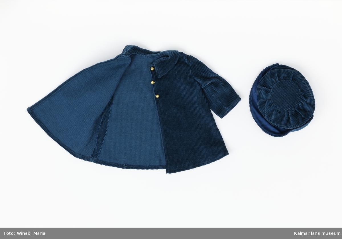 KLM 28082:133:1-2. Dockdräkt, dam, kappa och huvudbonad, båda av textil, bomull, grönblå manchester. :1 Kappa, tre runda, guldfärgade metallknappar framtill i rad. Knäpps med två tryckknappar. :2 Hatt, brätte framtill. Kulle, överst ett runt tygstycke, förstärkt med rund pappskiva insydd under, med smock, vilken rynkar hatten.