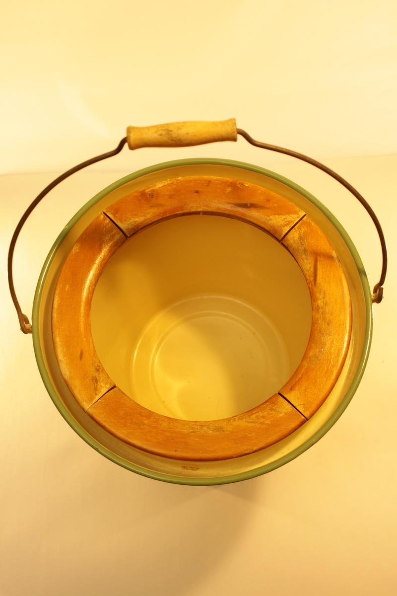 Emaljerad plåtpotta gul med gröna kanter. Pottan är i form av en hink med lock. Innanför locket ett sittring av trä. Hinken har även ett handtag med handgrepp i trä