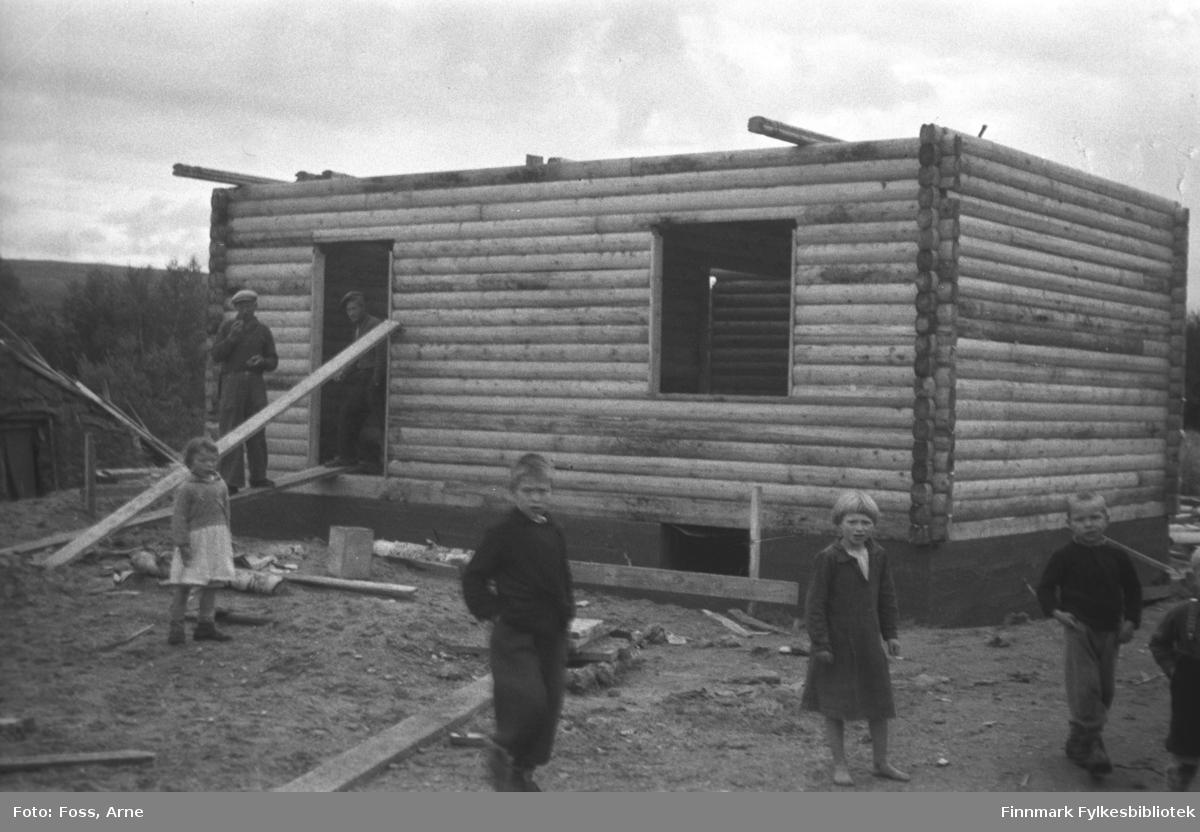 Et tømmerhus under bygging i Tana, i mai-juni 1947. Fem barn i forgrunnen og to menn ved døråpningen.
