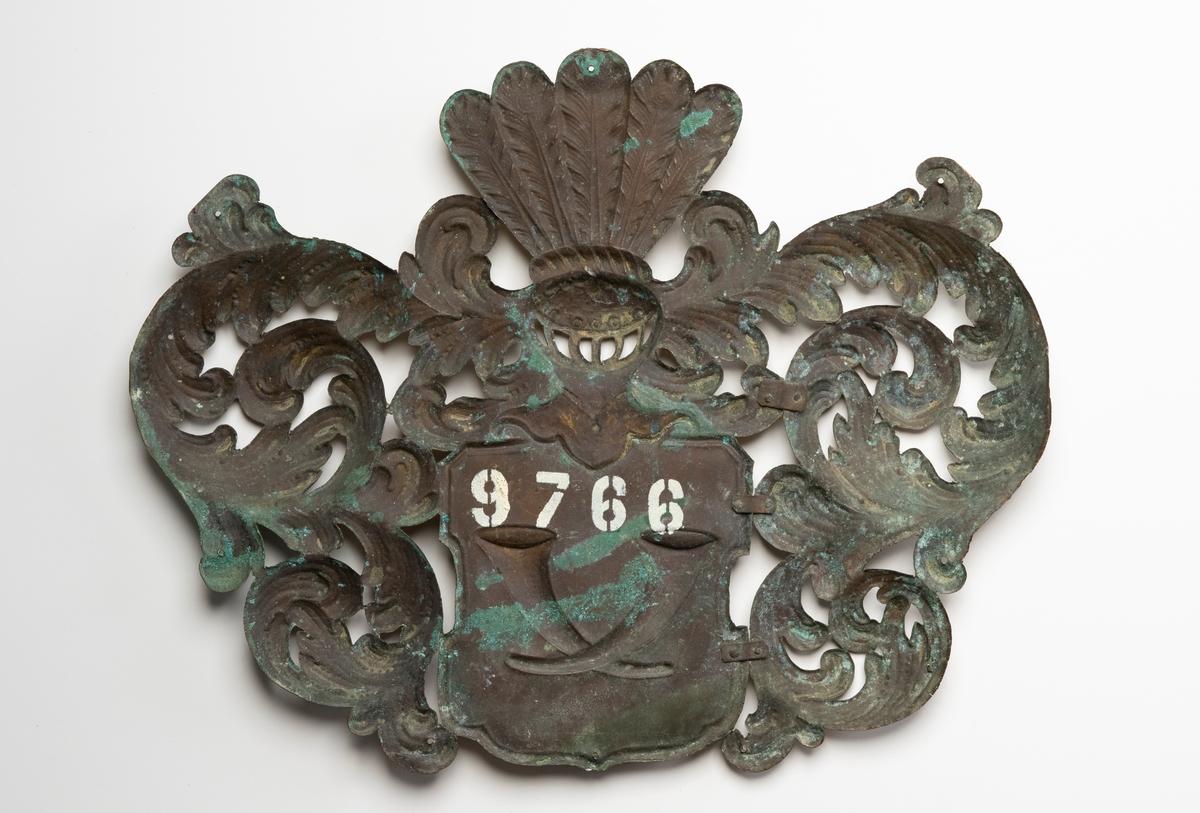 Kistplåt av förgylld koppar (?), delvis genombruten, i form av adelsvapen dekorerat med akantusblad. På själva vapnet sitter två korslagda horn.