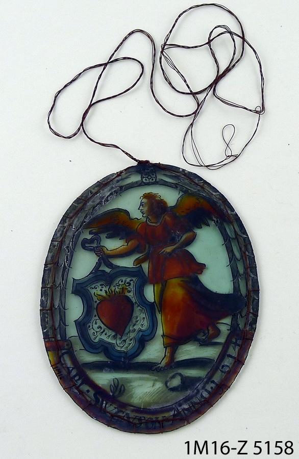 """Oval glasmålning föreställande ängel bärande stor vapensköld med brinnande hjärta. Motivet med ängeln inramas av ett rammotiv i grisaille samt text """"CARL.SWENSON.ANNO.1614"""". Glasmålningen har försetts med en textil hållare/inramning i brun tråd, oklart när det tillägget gjordes. Kanten på glaset är kröjslad."""