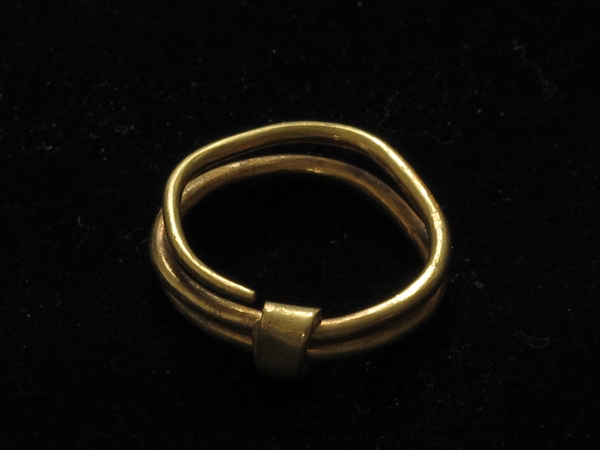 """Liten spiralring av fint gull på 2 + omganger, dannetav en temmelig tynn stang med rundt tverrsnitt. Rundt 2 omganger finnes en """"holder"""", dannet av en flat, rektangulær stang, som er lagt dobbelt på utsiden. Godt bevart. Tverrmål 1,9-2,1 cm. Vekt: 3,809 g."""
