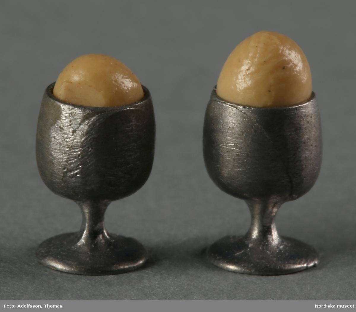 Två äggkoppar av metall med två kokta ägg av trä. Hör till inredningen i frukostrummet på första våningen i dockskåp NM.0331721+. och ska stå på det dukade köksbordet (NM.0333400a).