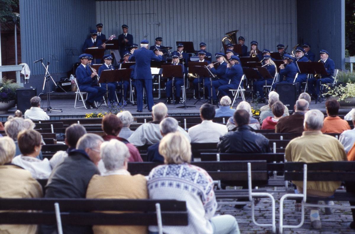 Arboga Blåsorkester, under ledning av Håkan Harrysson, spelar på sommaravslutning i Olof Ahllöfs park. Publiken sitter på bänkar framför scenen.