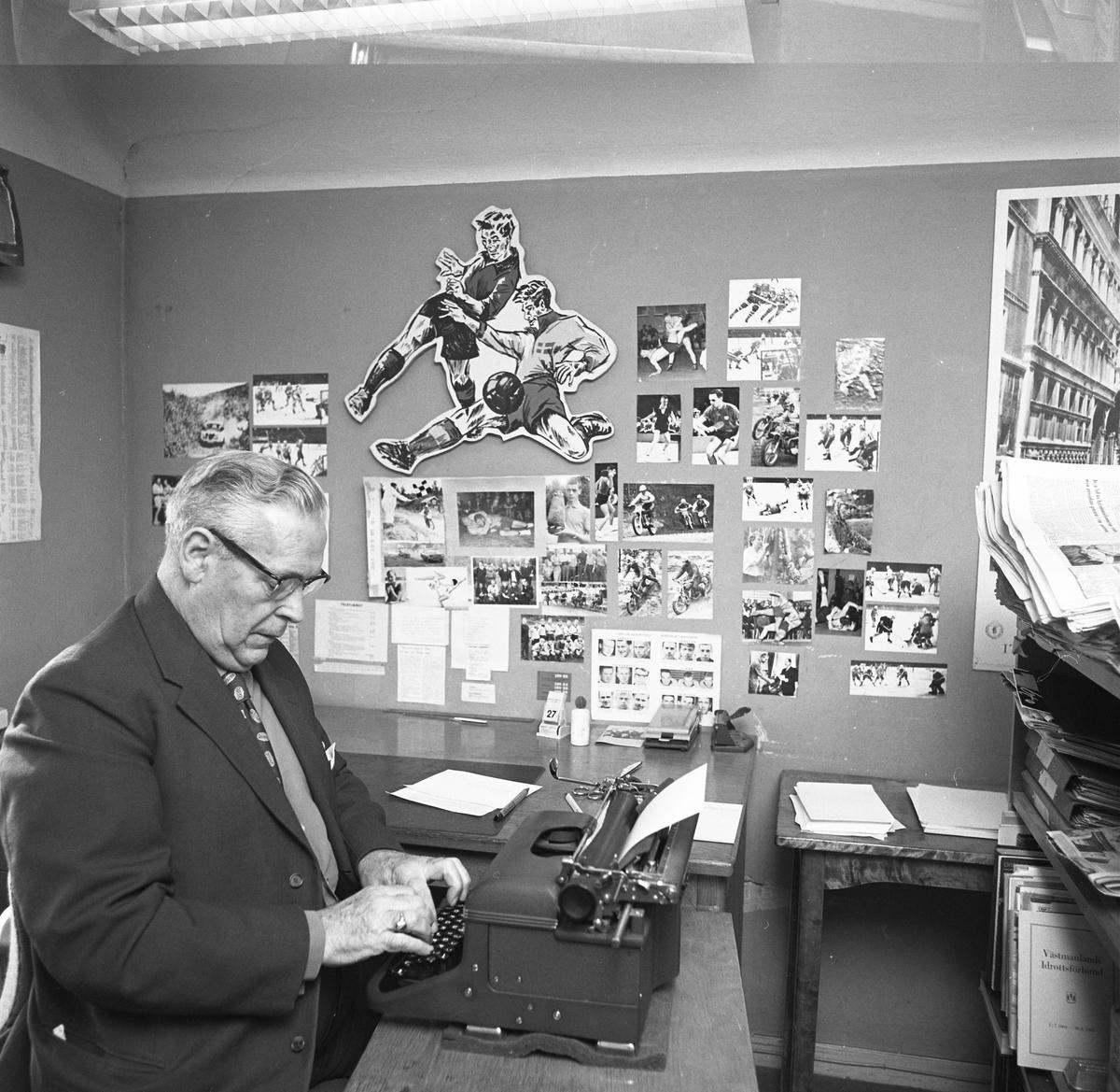 """Arboga Tidning, personal och interiör. Sportredaktionen. En man skriver på en skrivmaskin. På väggen finns diverse idrottsbilder. I bokhyllan, framför honom, står en skrift med titeln """"Västmanlands Idrottsförbund""""."""
