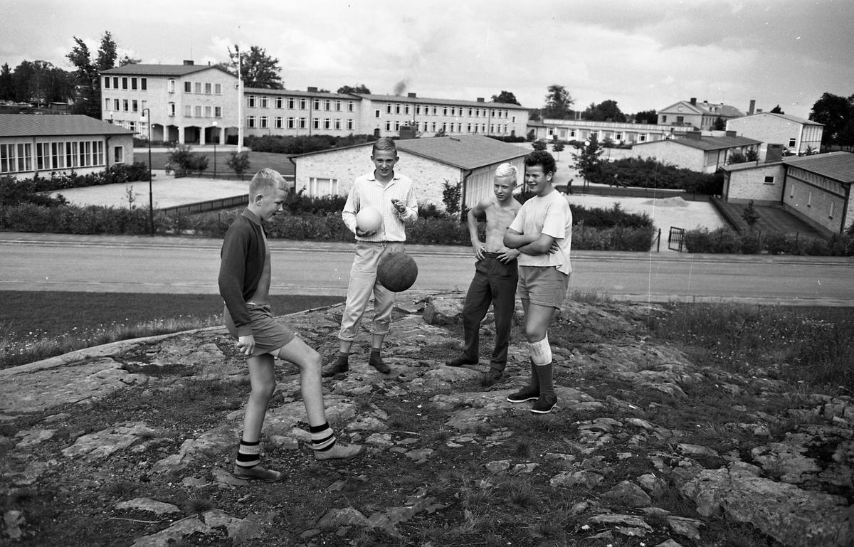 Fyra bollspelande pojkar; Anders Sköld, Åke Estmer, Urban Yttermalm och Göran Johansson. I bakgrunden ses Gäddgårdsskolan. 1960-talet
