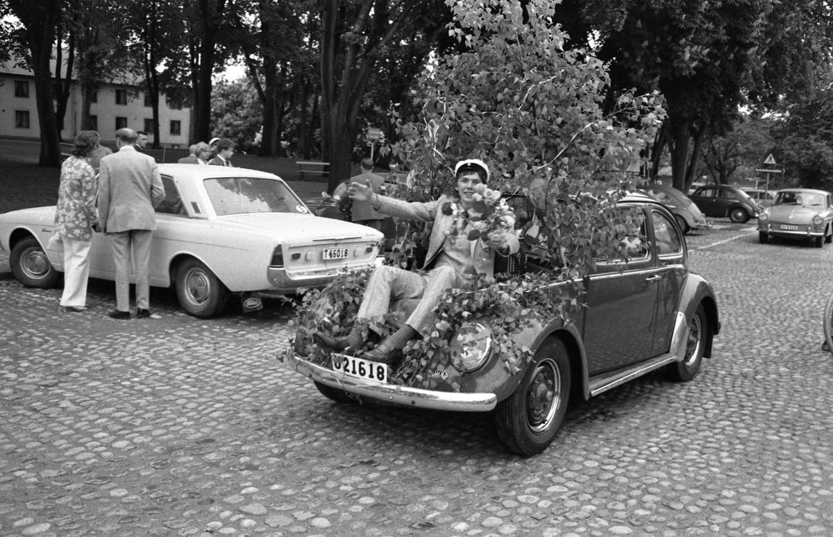 Studentdag! Anders Hellström körs runt i framluckan på en Folkvagn. Bilen är dekorerad med björklöv och Anders är dekorerad med studentmössa och blommor. Ungdomar, i musikkåren, har fullgjort sitt uppdrag.