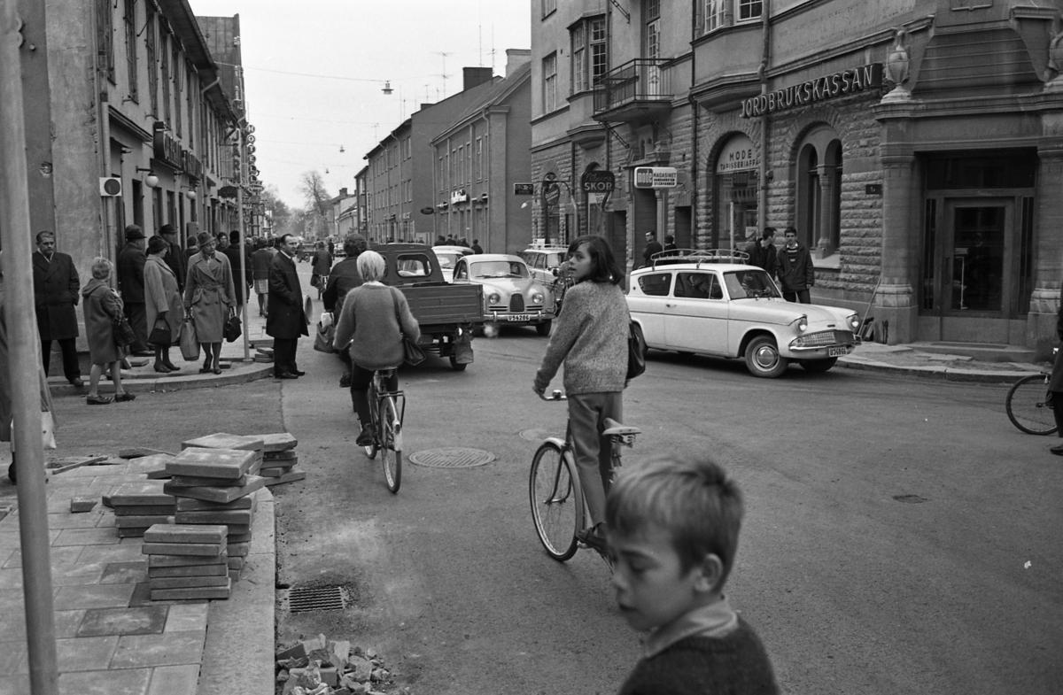 Trafik på Nygatan. Många bilar, människor som promenerar, en cyklist. Till vänster ses Öhrman & Melander, Järnaffären och hotellet. På höger sida ligger Olssons, Nilssons skor, Modemagasinet och Jordbrukskassan. I förgrunden ligger stenplattor. Trottoaren har gjorts iordning.