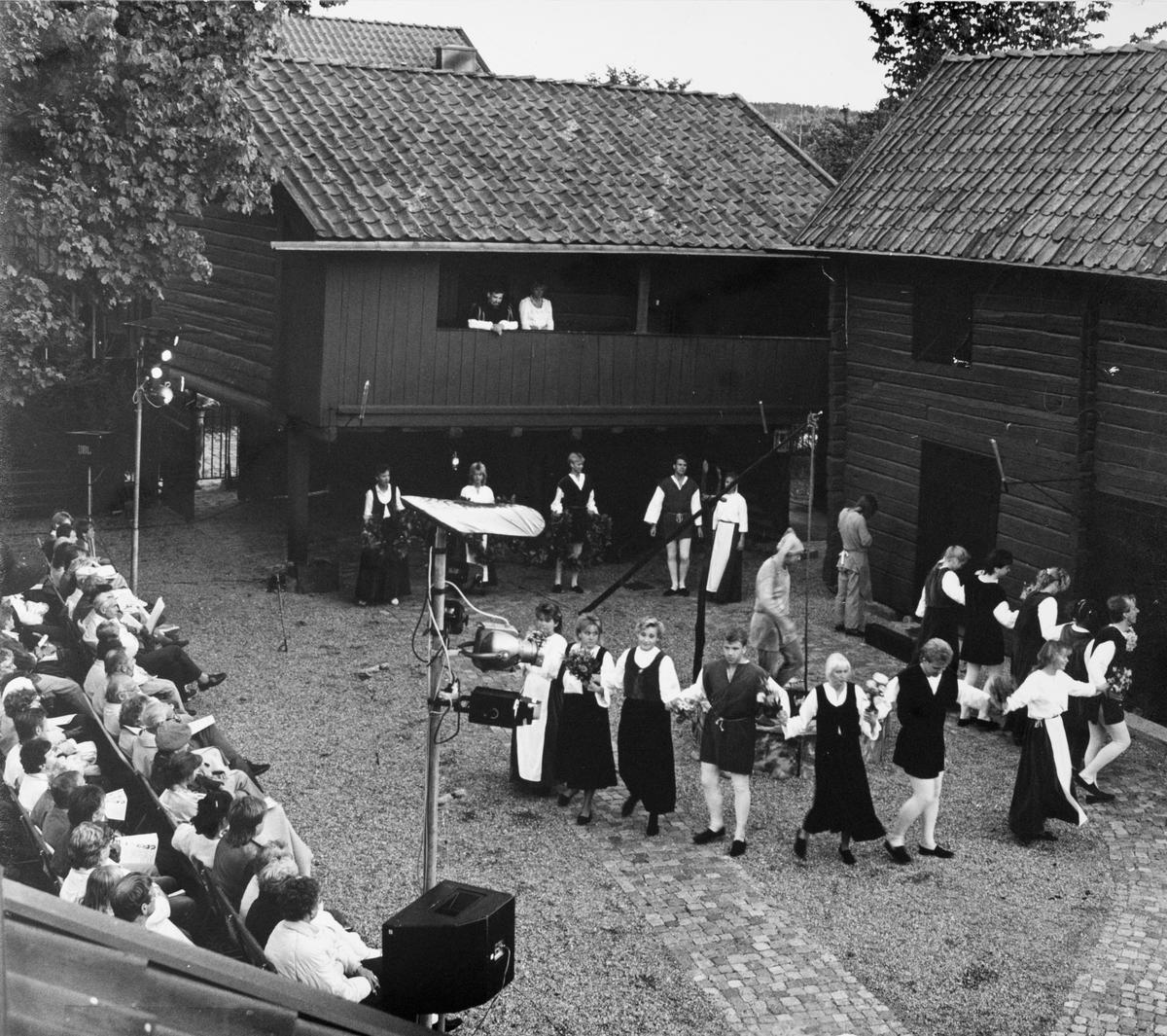 """Giv oss fred, även kallat Arbogaspelet, spelas på museets innegård. Publik och aktörer. På loftgången står Engelbrekt Gertsson, spelad av Stig Eriksson. Aktörerna dansar i ring på gården. På brunnskanten dansar gycklaren /narren spelad av Sven Gustav Petri. Giv oss fred är ett teaterstycke skrivet av Rune Lindström 1961. Handlingen, som är inspirerad av Arbogas klosterhistoria, är förlagt till början av 1500-talet. Uruppförandet skedde den 11 augusti 1962 och Rune Lindström spelade Engelbrekt Gertsson. Lions Club i Arboga stod för arrangemanget. Föreställningarna regnade bort och det blev ett stort ekonomiskt bakslag för föreningen. Spelet har framförts igen; 1987, 1988, 2012 och 2015 av medlemmar i """"Bygdespelets Vänner""""."""