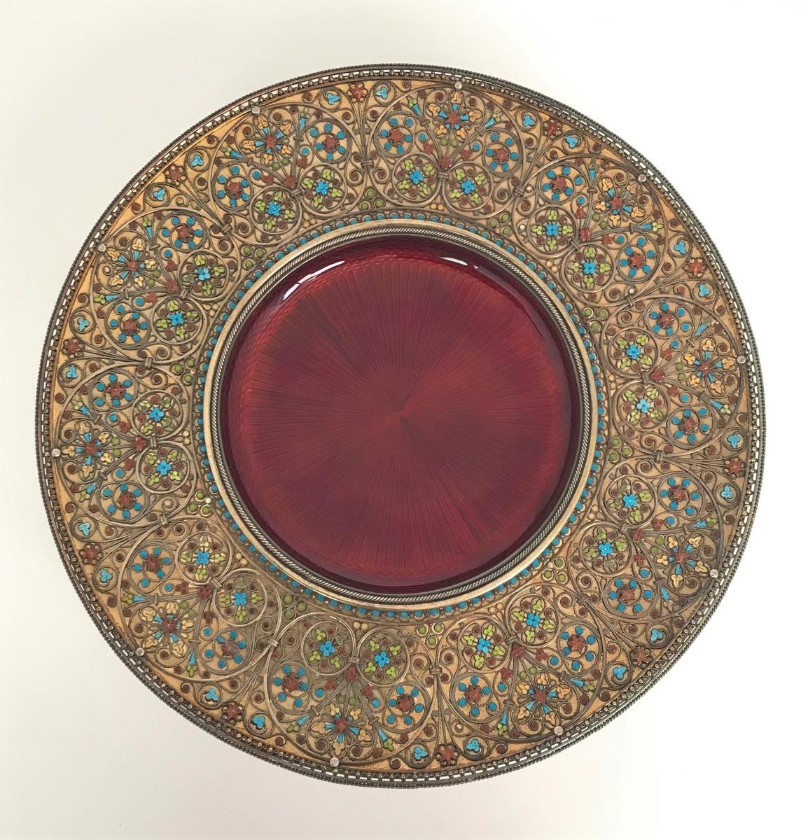 Et lavt sirkulært fat som hviler på en stett. Skålen er utført i forgylt sølv og emalje. Innsiden er gravert og dekket med speilemalje i en dyp rødfarge. Den brede kanten er overspunnet med et intrikat nyromansk rankeornament i patinert sølvfiligran. Mellom filigransarbeidet er flaten dekket med små rosetter og blader i grønn, rød, blå og gul emalje.