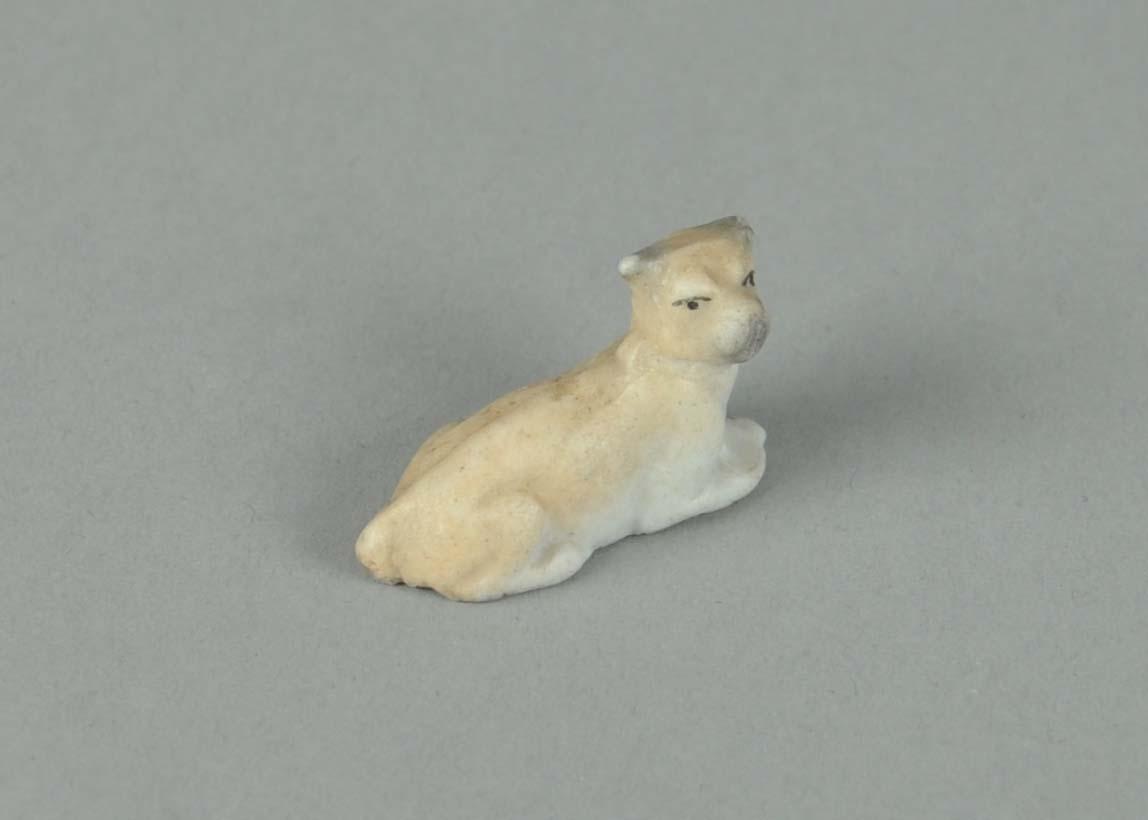Fire hundefigurer av porselen. En hund står på alle fire og har glassert keramikk. To hunder ligger, og en hund står på bakbeina.