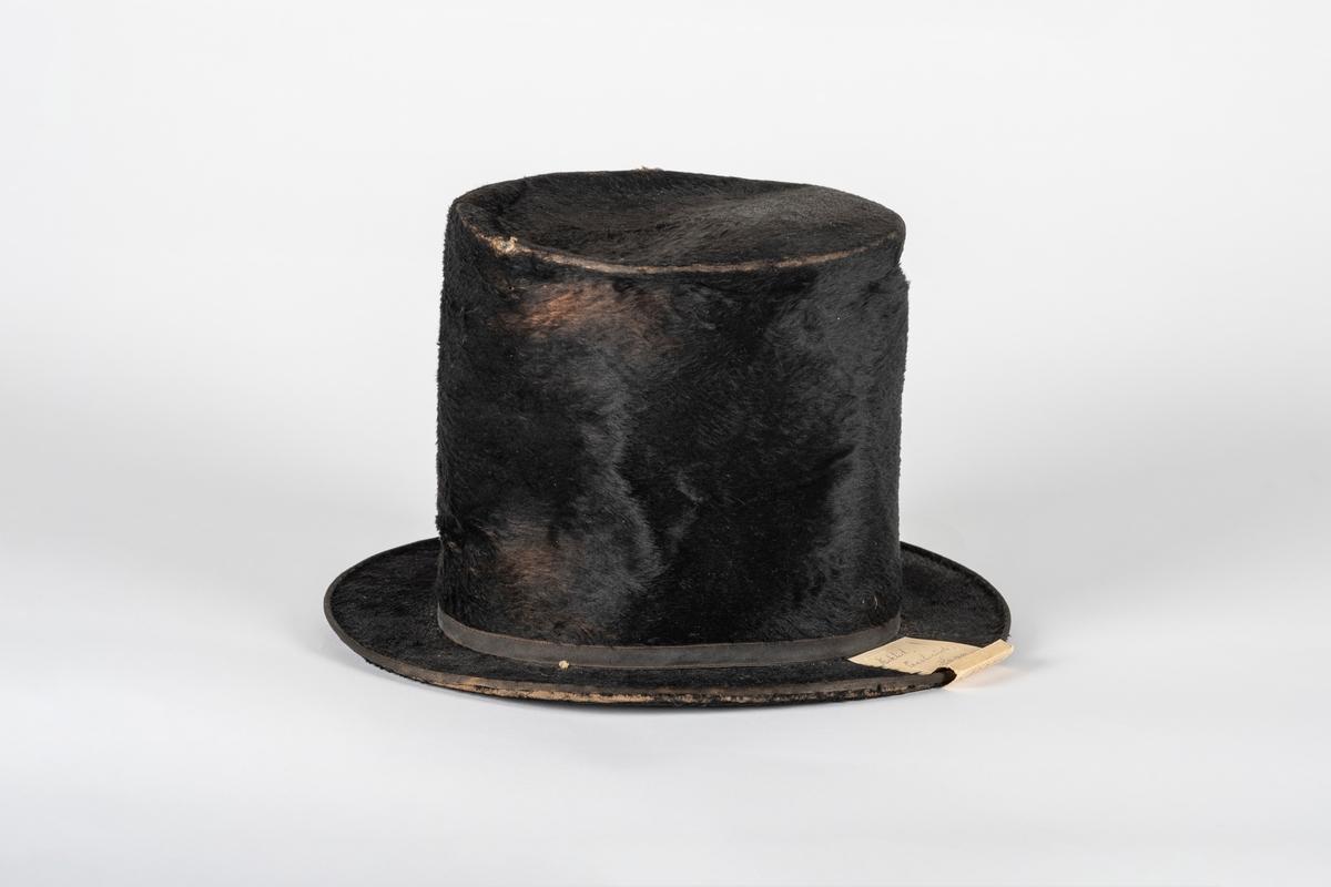 Svart flosshatt med høy sylinderformet pull og smal brem. Hatten er trukket med felpel. Nederst på pullen er det ripsbånd med sløyfe. Pullen er fòret med papir og har svettebånd av malt lerret. Bak svettebåndet er det bomullsvatt.