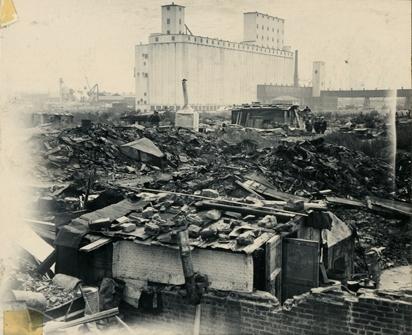 """Oversiktsbilde som viser noen av boligbrakkene i """"Ørken Sur"""", Brooklyn NY, ca 1929-1935. Stor, hvit fabrikkbygning i bakgrunnen."""