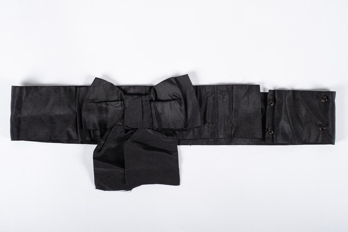 Svart ripsvevd belte med sløyfe. Det er påsydd to spiler på beltet, en på innsiden og en i enden. Den har fire trykknapper hvor hanndelen mangler.