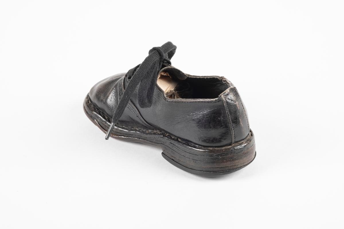 Et randsydd barnesko (høyre sko) av lær. Skoen har snøring med flate lisser. Maljene er av metall. Sålen er av lær og er forsterket med spiker på hælen og ved tuppen på undersiden.