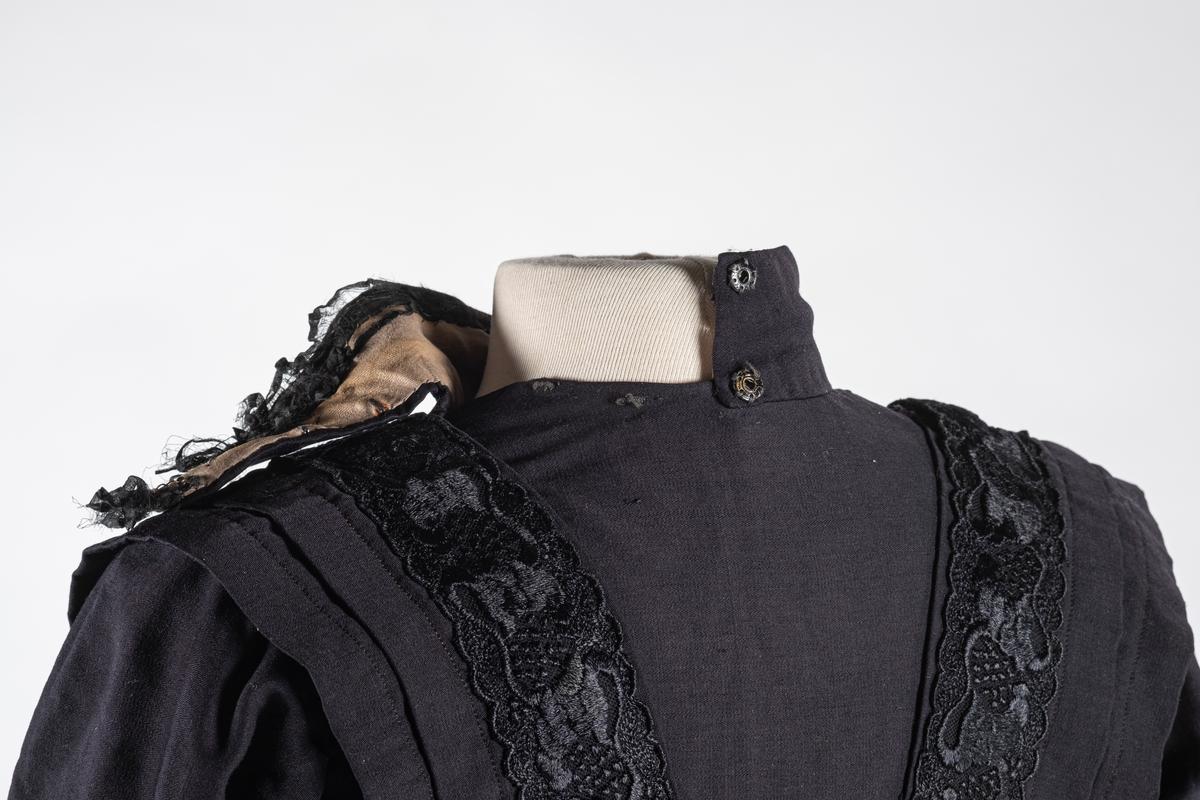 Kjoleliv i svart bomull med lilla fôring. Kjolelivet har doble ermer. Nedre del på innerermen har opphøyde vertikale sømmer. Det samme har den midtre delen (klaffen) av forstykket. På hver side av klaffen er det påsydd blonder som strekker seg over skulderen og nedover ryggen i en V form. Langs disse blondene er det folder. Det er påsydd to svettelapper ved underarm-partiet og hempe ved hvert ermehull på innsiden. Kjolelivet har også fire spiler på innsiden. Kjolelivet lukkes med metallhekter og trykknapper. Fôret har egen lukning før ytterstoffet lukkes over. Halsen er høy og kneppes på baksiden med trykknapper. Det er to hekter på baksiden som skjørtet skal hektes i.