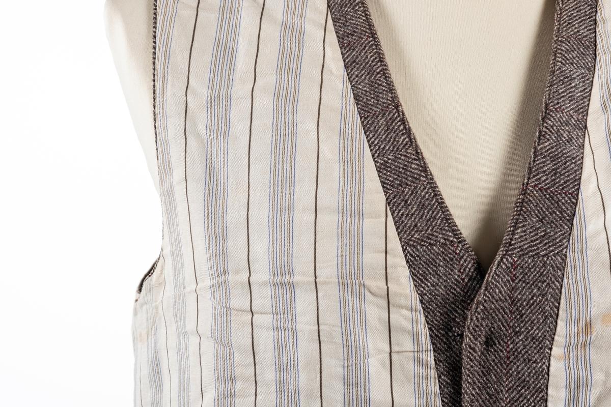 Vest med forstykke i brun tweedstoff og bakstykke i brun silke. Den har foring i stripete stoff. Den lukkes i front med seks knapper, og har fire forlommer.