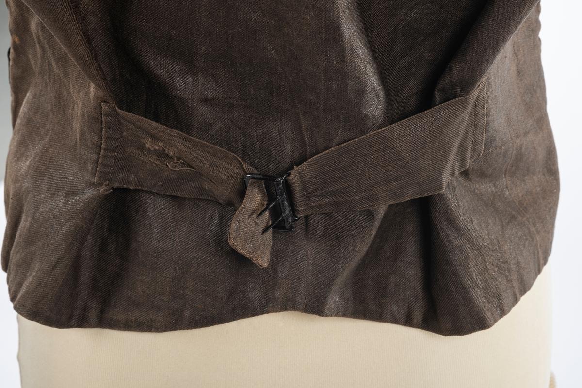 Vest med forstykke i silke og bakstykke i bomull. Den er foret med lin. Det er dobbelspent knepping og spensel i rygg. Knappene er trukket med silke.