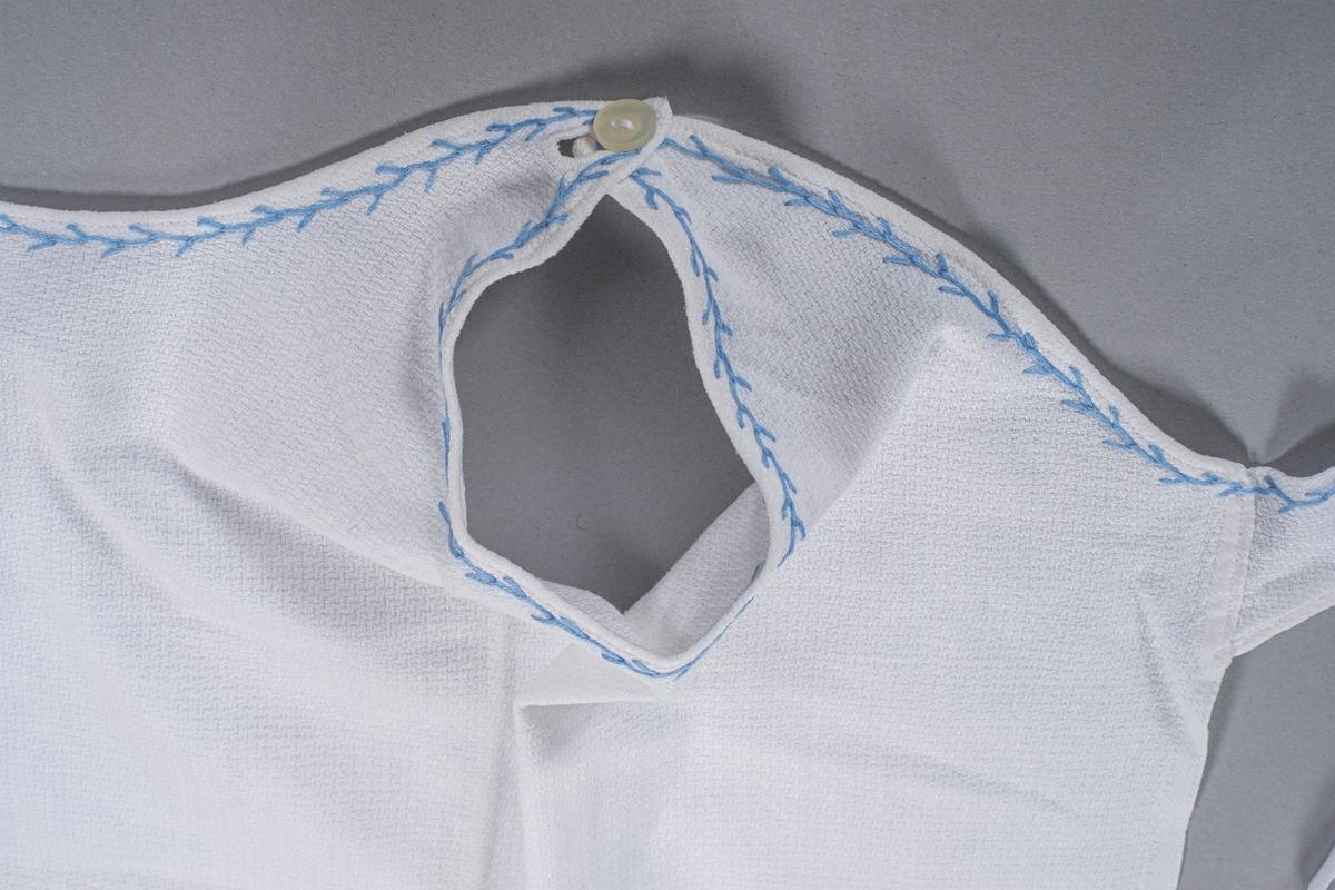 Åpning hele veien bak. Ermeløst bærestykke som overlapper bak. Bendelbånd er sydd på bak på bærestykket. Ett av båndene tres gjennom et hull i bærestykket på høyre side slik at man kan knytte sammen båndene rundt barnet. To bendelbånd er sydd på nederst bak, en på hver side. Enkelt broderi rundt erme- og halsåpning. Bærestykket lukkes med en knapp over hver skulder. Stoffet som er brukt er mønstervevd bomull.