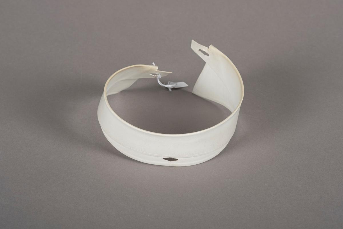 Hvit snipp som er foldet, stivet og bøyd. Snippen har knappehull i hver ende og en knappehull i midten. Den er belagt med plast.