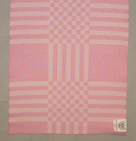 Rutig löpare, två stycken, vävd i varprips en i rosa och en i svart. Det är blekt och färgat tvåtrådigt bomullsgarn i varpen och blekt tvåtrådigt bomullsgarn i inslaget. De smala fållarna är tråcklade.  Den rosa löparen är märkt R15:1 och den svarta R15:2.  Löparen med modellnamn Golv är formgiven av Ann-Mari Nilsson och tillverkad av Länshemslöjden Skaraborg. Den finns med  på sidan 38-39 i vävboken Inredningsvävar av Ann-Mari Nilsson i samarbete med Länshemslöjden Skaraborg från 1987, ICA Bokförlag. Se även inv.nr. 0001-0014,0016-0040.