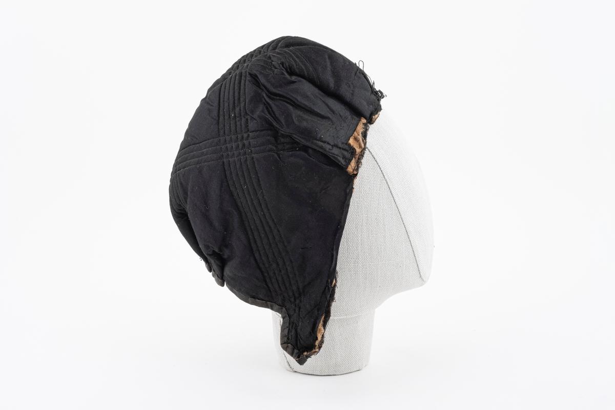 Kyseformet lue. Delen som vender ut er i silke; fôret som vender inn er  i ull. Vattering med stikninger i linje-/rutemønster. Selve vatteringen ser ut til å være i noe blandingsstoff av ull og annet organisk materiale. Hører etter all sannsynlighet sammen med GH.03313, som er en krage i samme materiale og utførelse. Kragen har en pelskant som har omsluttet den fremre kanten på luen. Luen og kragen har sittet sammen i nakkepartiet.