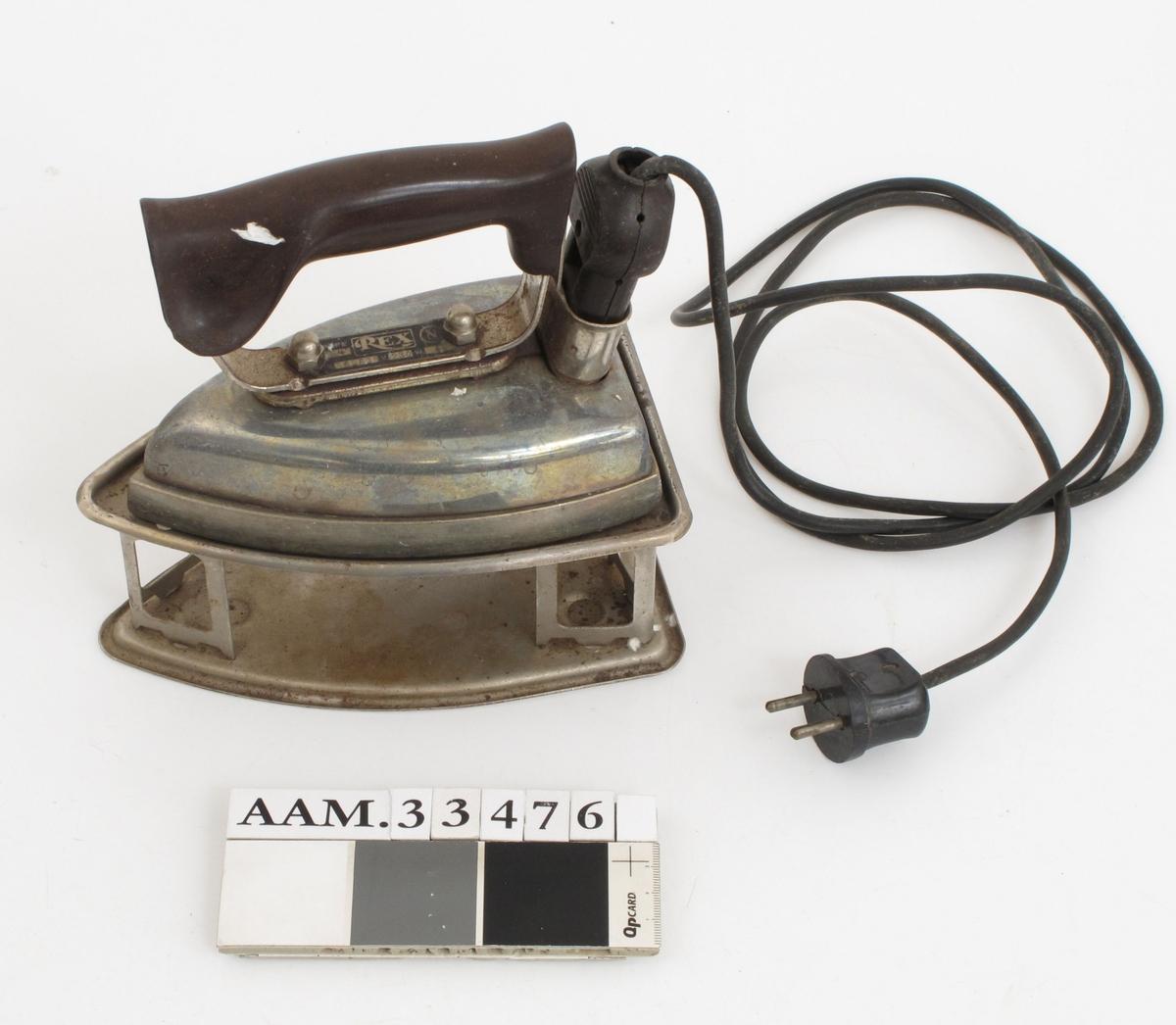 Elektrisk strykejern med fot. Handtak av bakelitt. Både strykejern og fot er stemplet Rex.  a. Strykejern med el. ledning b. Fot, av jern.