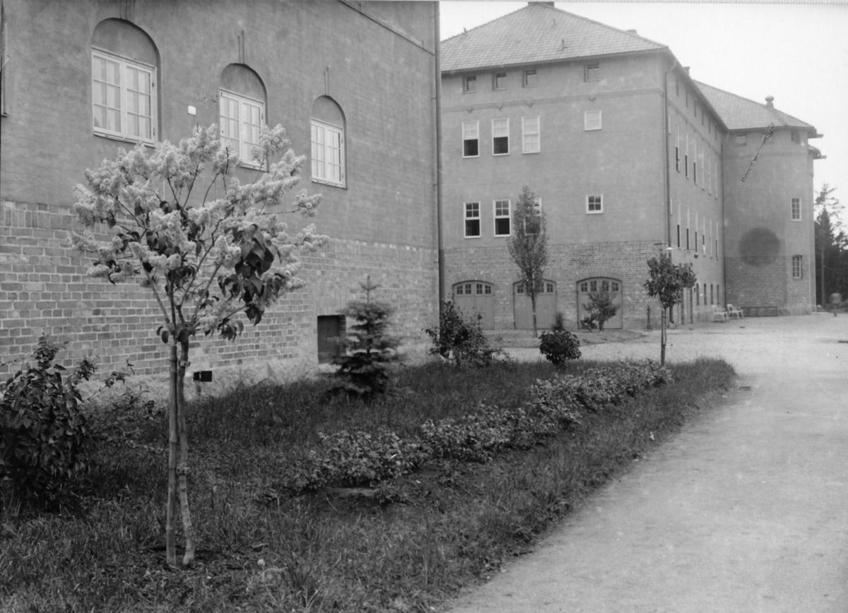 Kasernvakten 1925  Post vid grind 1. Här skedde inpasseringen till regementet fram till slutet av 1950-talet, då ny vakt byggdes i kasern 004 och grind 2 blev infartsgrind. Fönstren på långsidan var till arrestens celler. Byggnad: K0074-008  I bakgrunden syns kasern 006 -- avsedd för 9.- och 10. komp i 3. bataljon. Strax efter freden 1918 ändrades infanteriets organisation och den tredje bataljonen ströks. Så den hitre delen användes för 9. komp, vilket var ett handräckningskompani, och den bortre delen blev regementssjukhus.  OBS! två bilder.