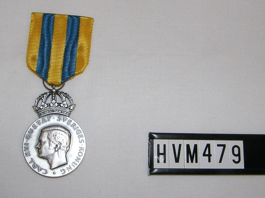 Rund medalj med kunglig krona och babd.