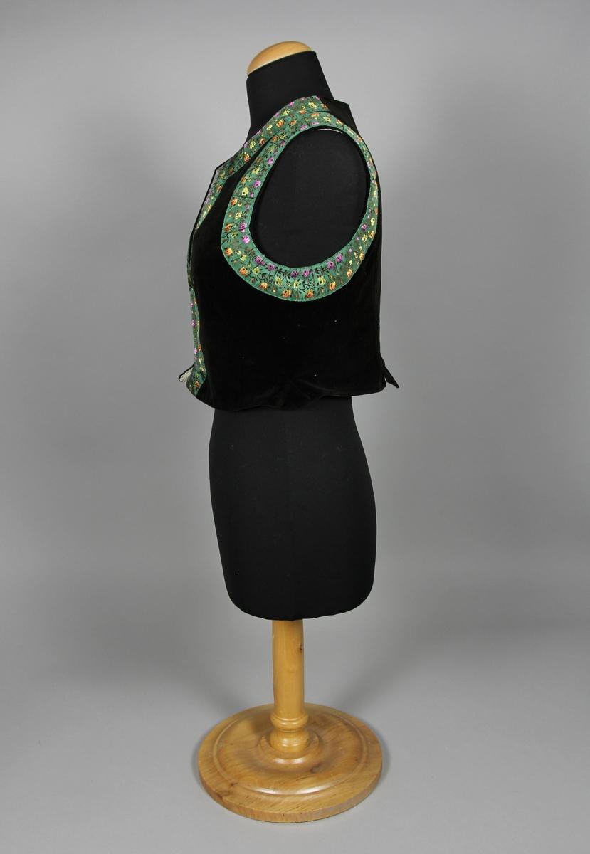 Livstycke av mörkt brun sammet. Kantad med breda blommiga band med grön botten längs framkant, halsringning och ärmhål. Stängs fram med hyskor och hakat.