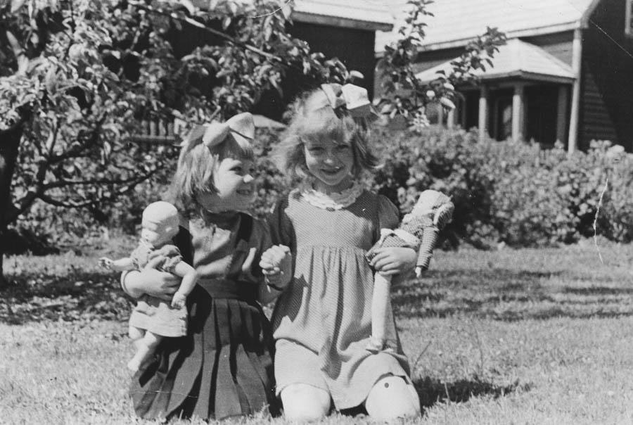 To små jenter på gresset med dukkene.