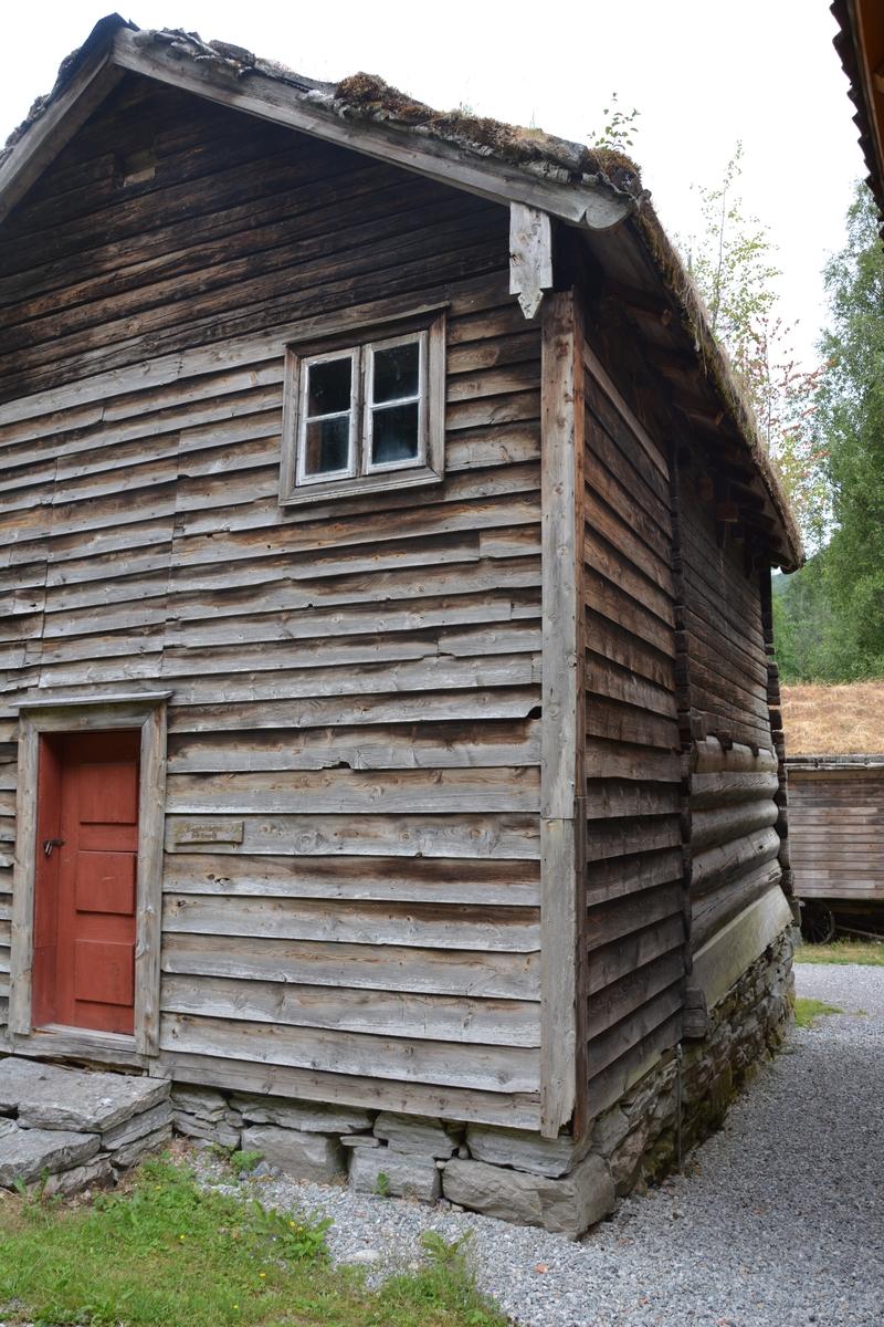 """Lafta bygning i tre etasjer med tørrmur og torvtak. Skot og gang av reisverk og supanel. Ingen eldstad. To glas i fremste gavlen med skåprom mellom. Eit rom i kvar høgd med ein gang/""""dør"""" framfor, og trappa går mellom desse. Første høgda var bu/ forrådsrom (ikkje nystove). Bua er den eldste delen av bygningen. Andre høgda er sett opp seinare, med mykje grannare tømmer enn første høgda. Bua har ovalt tømmer, rette, ikkje avsmalnande ovale novhovud og 6-kanta laftehals. Syllstokken har høgt, trapesforma tverrsnitt. Døra er einfeld med den gamle beitskitypen, med spor der dei tilspissa endane på veggstokken går inn. I stokken over døra er det til begge sidene eit par opningar som kan likna på spor etter bjelkar, men er truleg gluggar (den eine har hatt skyveluke på innsida). Stokken over gluggane er nyare, slik at vi ikkje har heile den opphavelege forma deira. Stokken som gluggane er hogne i, har likevel også merke etter bjelkar, eit grunt spor over døra og eit djupt ute ved langveggen. Midt etter rommet må ha lege ein bjelke. Det ter etter han i motsette gavlen òg. Ved langveggen held stokken med hogga fram med eit utstikk ut i svala på denne sida. Forma på utstikket er heilt som på ein stokk som pla liggja under ei utstikkande stavlægje, dvs. øvste stokken i langveggen. No ligg han i tverrveggen over døra. Tilsvarande utstikk er det også i den ytre tverrveggen. Dette og meir til fortel at dei har gjort ein god del med bua då dei bygde henne saman med loftet. Mest sannsynleg har dei snudd henne, slik at langvegg vart tverrvegg. I gavlen motsett døra er det skore ut ein glugge som er teken ut av to stokkar og spor etter eventuell eldre opning er her bortkome . I svilla i same gavlen er spor etter fire bjelkar på utsida. Det er truleg etter golvet i ei sval frå før dei to høgdene var samanbygde. Då kan det ha vore ei sval på eine langveggen. Andre høgda er yngst. Ho er sett opp med mykje grannare tømmer enn første høgda, og hoggemåtane skil seg også mykje ut med sine f"""