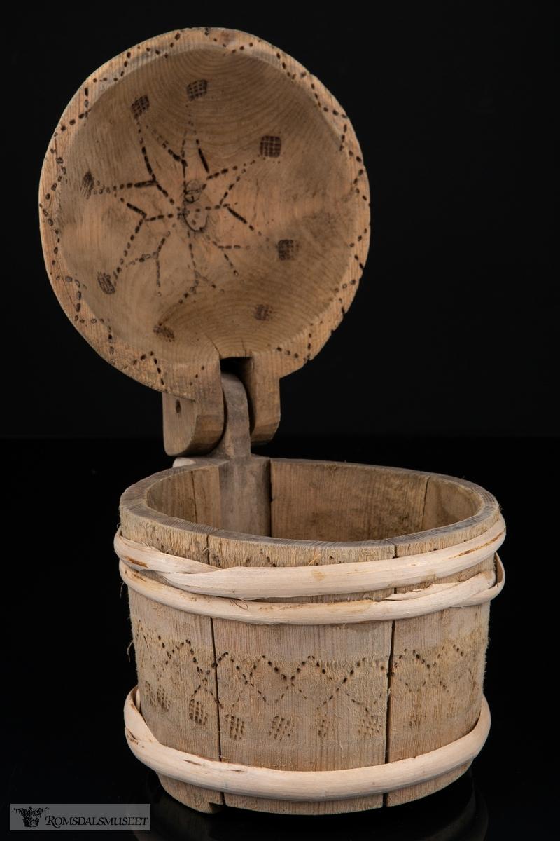 Rund, lagget smørkanne som står på tre korte føtter i forlengesle av stavene. Avrundet lokk med knott som er hengslet på hanken, som er skåret ut som en del av den bakerste staven. Omslått med gjorder oppe og nede.